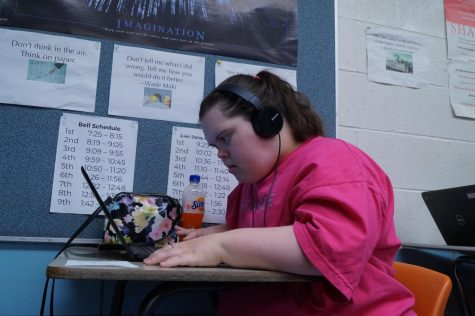 Bailey Graham looking at her laptop while wearing headphones.