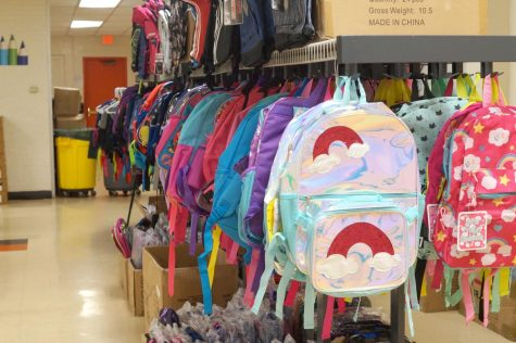 Colorful backpacks hang on a rack. A rainbow backpack is shown in the foreground.