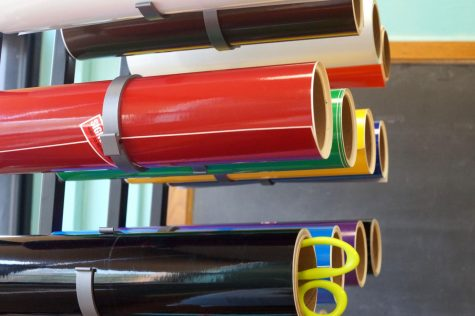 Colorful tubes of plastic sit in a rack. One has a pair of scissors in it.