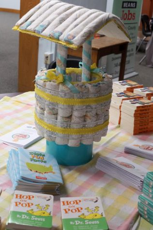 A well made of diapers is surrounded by books about babies.