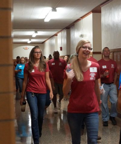 Volunteers in red shirts walk down a hallway.