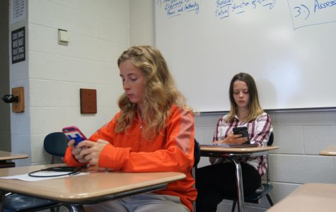 Kimmy Cane (12) and Athena Patton (10) sit in house on their phones.