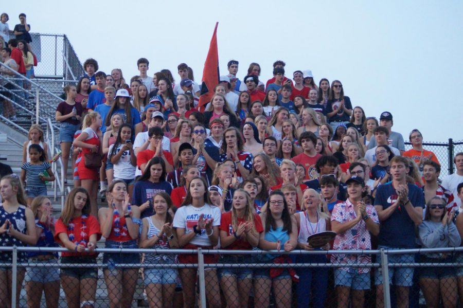 Sophomores, Juniors, and Seniors student sections cheering on the Hayes football team in there USA gear.