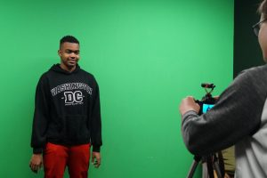 student in front of green screen.