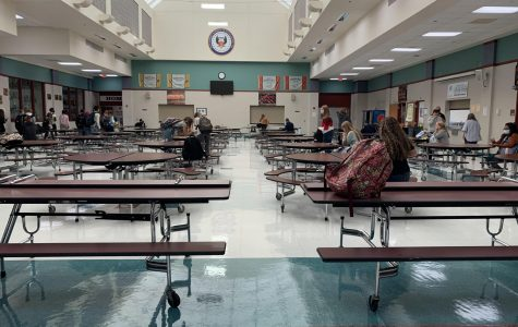 Photo of cafeteria with tables spaced six feet apart.