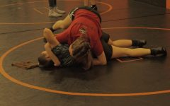 Junior's Jamie Hake and Maddie Wells wrestle with each other in practice.