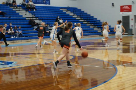 Hayes basketball player dribbles down the court.