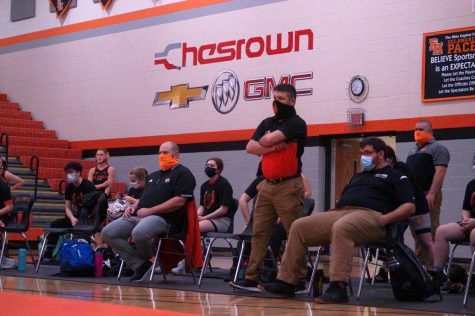 Wrestling coach NAME supports and watches his team from the sidelines. NAME congratulates his team whether they win or not.
