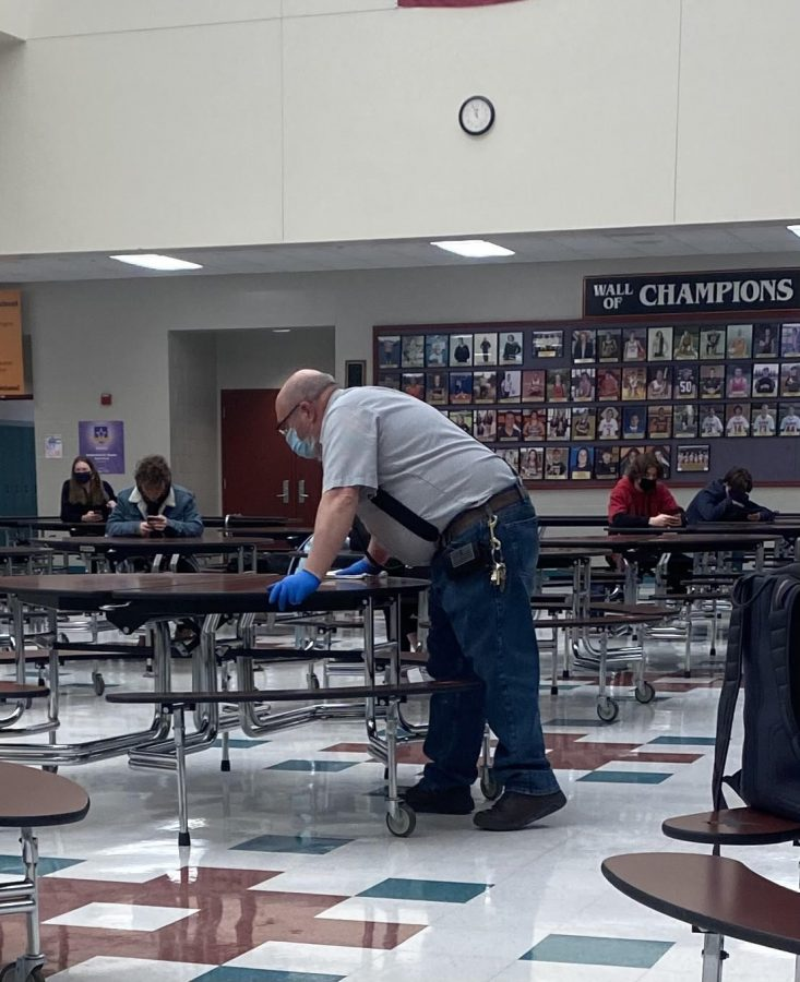 custodian sanitizes a cafeteria table