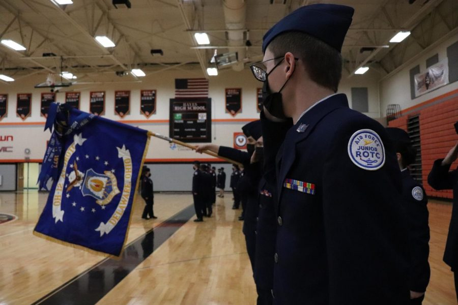 Junior Owen Morris standing next to the Delaware AFJROTC flag
