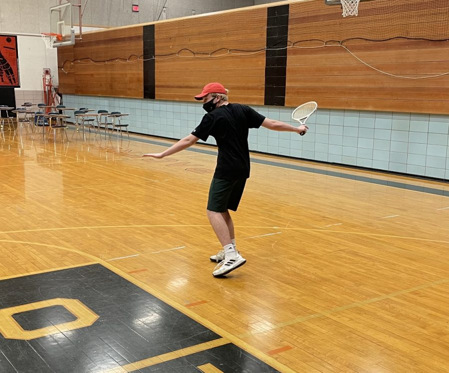 Junior Joe Molina hits groundstrokes at tennis practice.  On rainy or exceptionally cold days, the boys' tennis team uses the gymnasium to review foundational skills.