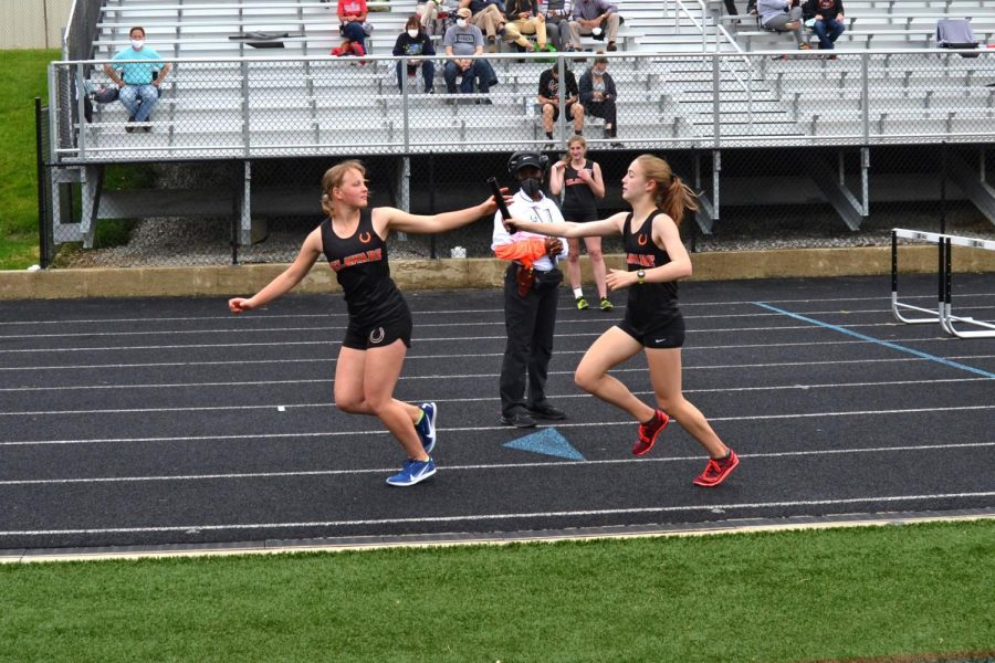Sophomore Rowan Hering hands off the baton to freshman Ella Fronduti in the 4x800 relay.
