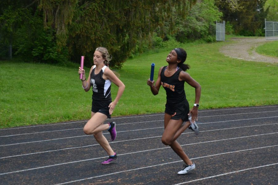 Student athletes from two different teams running relay next to each other