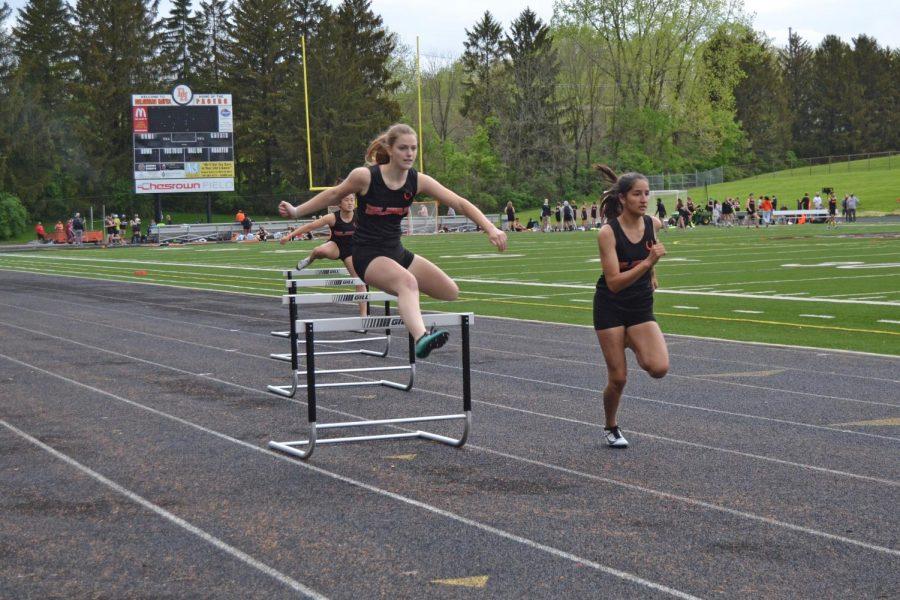 Senior Caylee Combs clears hurdle in 300 meter hurdles.