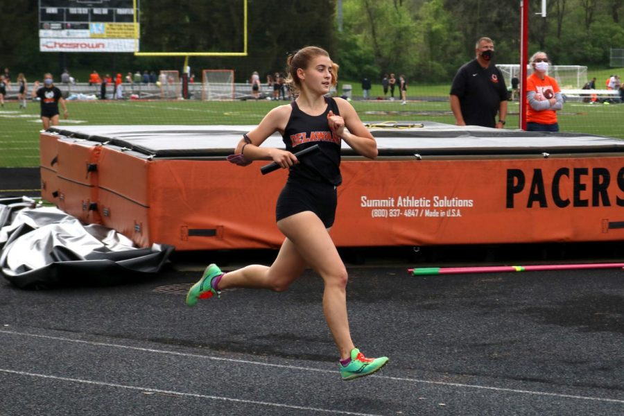 Student athlete running with relay baton mid stride