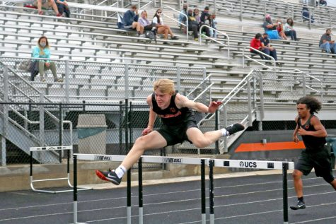 Two athletes clear hurdles
