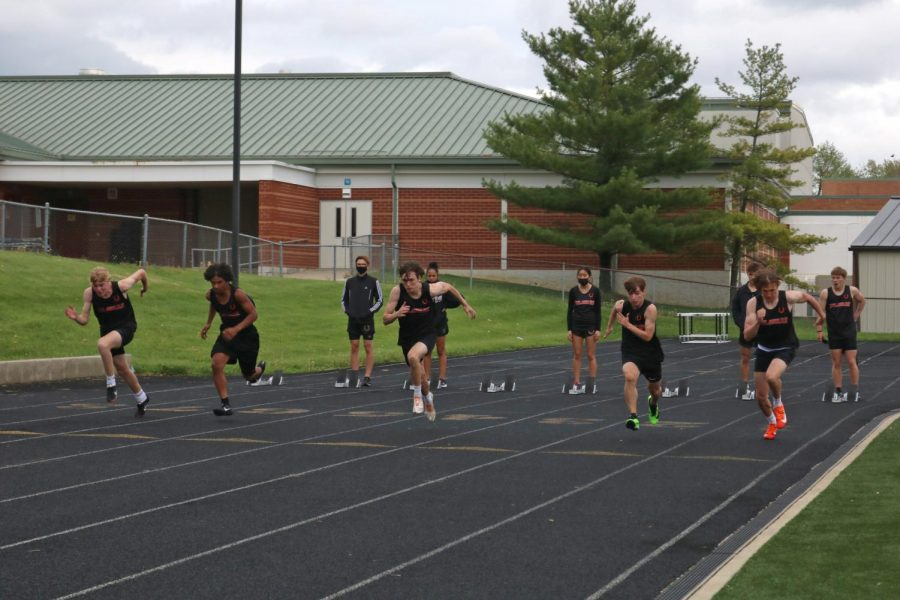 Multiple student athletes take off from starting line