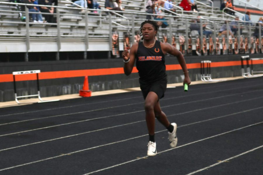 Student athlete running relay with baton