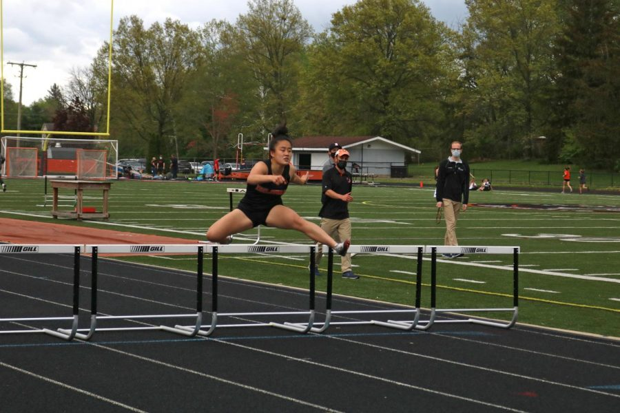 Runner jumps over hurdle