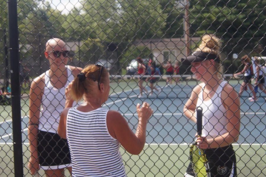 Seniors Sophia Midura and Eliza Riggs discuss strategy with coach Dede Hibinger.