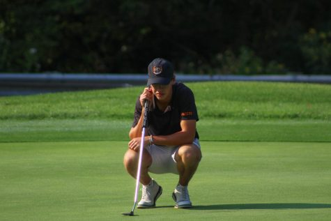 golfer squats down to read his putt.