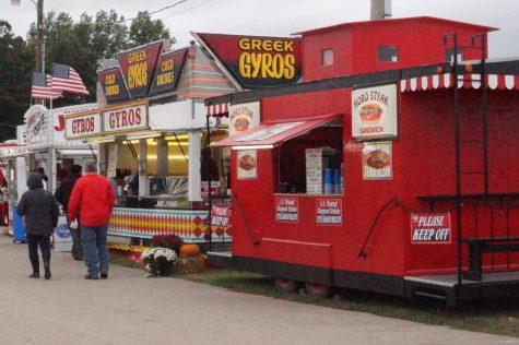 People walk past a variety of food trucks.